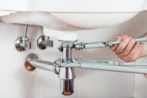 A plumber tightens loose pipes under the bathroom sink