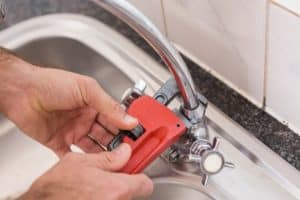 A plumber tightens a leaky faucet with a pipe wrench
