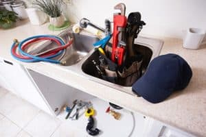 A plumbers tools and assorted hardware in a kitchen sink