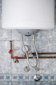A wall mounted water heater on a tile wall