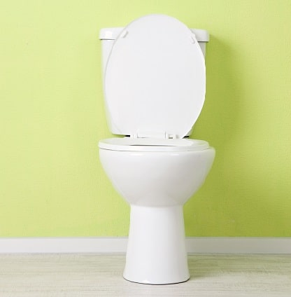 A white toilet with a green wall
