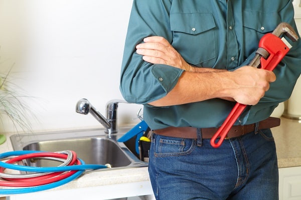 Plumber in a kitchen addressing plumbing issues