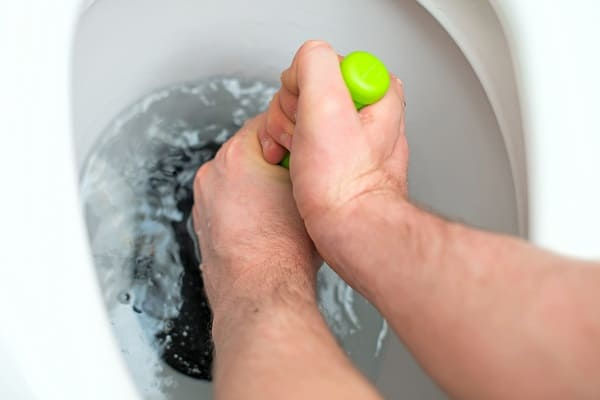 A man tries to unstop his toilet with a plunger