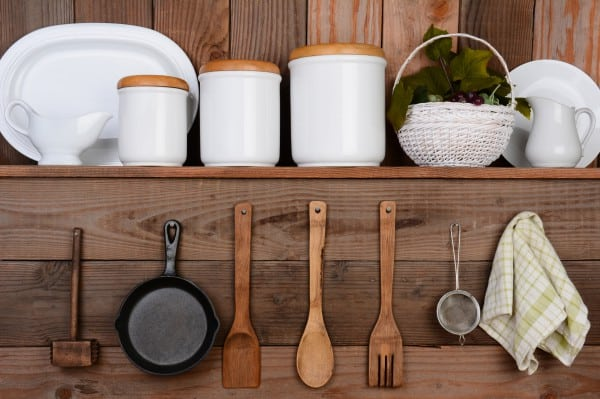 A bunch of dishes and a plant sit on a shelf and some wooden spoons, a pan, a sifter, and a washcloth hang on nails underneath